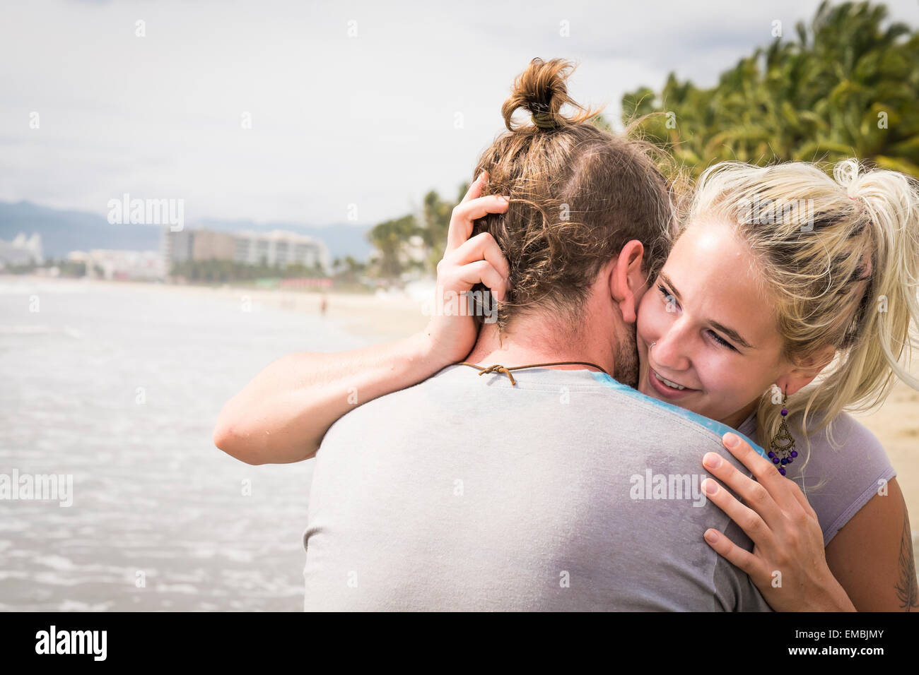 Young woman hugging young man, smiling, at a beach. Riviera Nayarit, Pacific Coast, Mexico - Stock Image