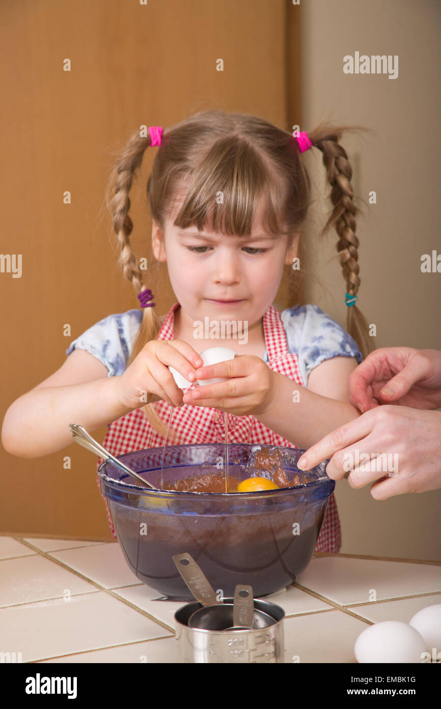 Five year old girl breaking an egg into a mixing bowl to become a chocolate bundt cake later, with dismay at the - Stock Image