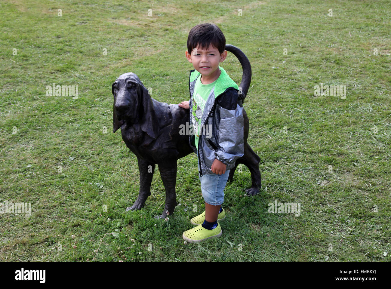 It's a photo of a kid with a black dog statue in a park or garden - Stock Image