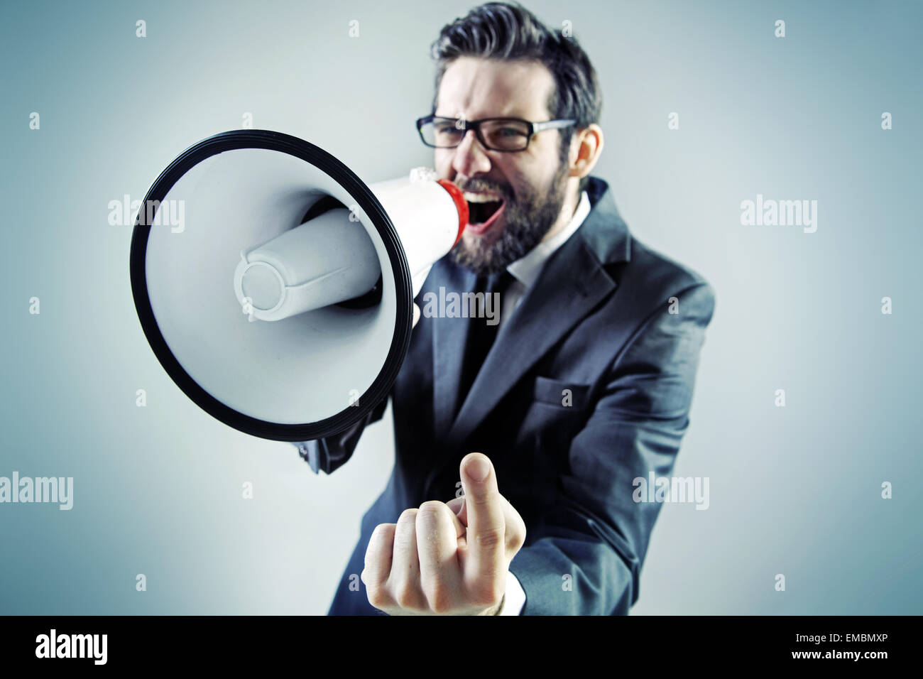 Aggressive young businessman yelling over the megaphone - Stock Image