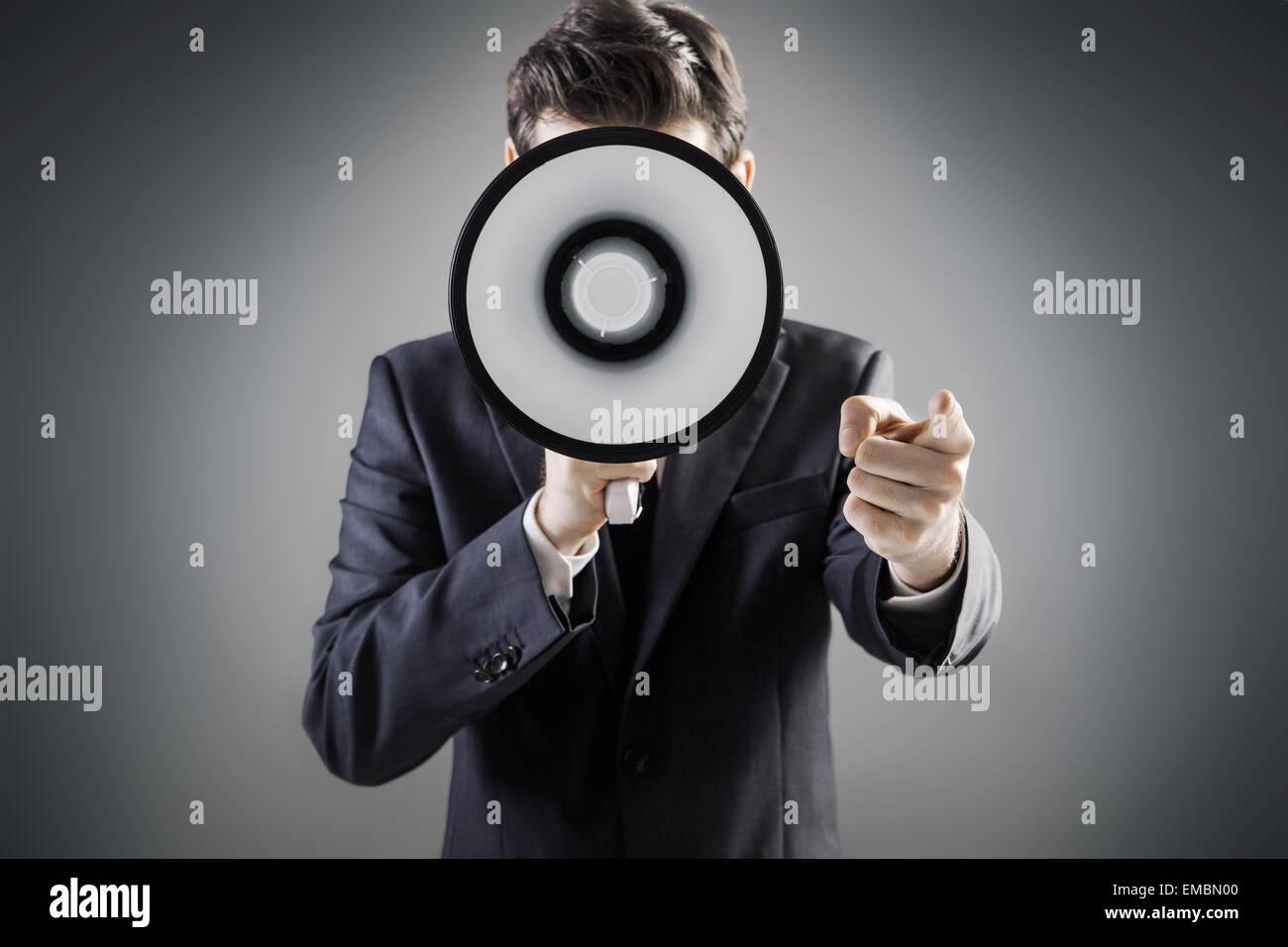 Elegant manager holding a huge megaphone - Stock Image