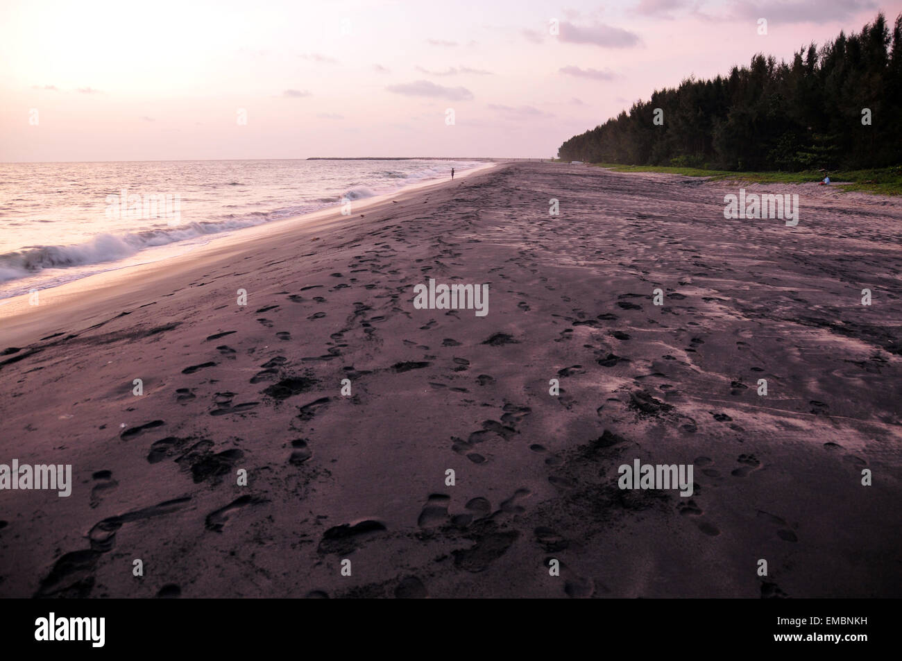 impression of human legs on a black sea sand shore. - Stock Image
