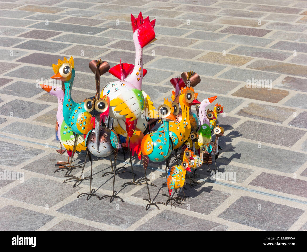 Brightly painted metal bird garden ornaments on sale in a weekly market - Stock Image