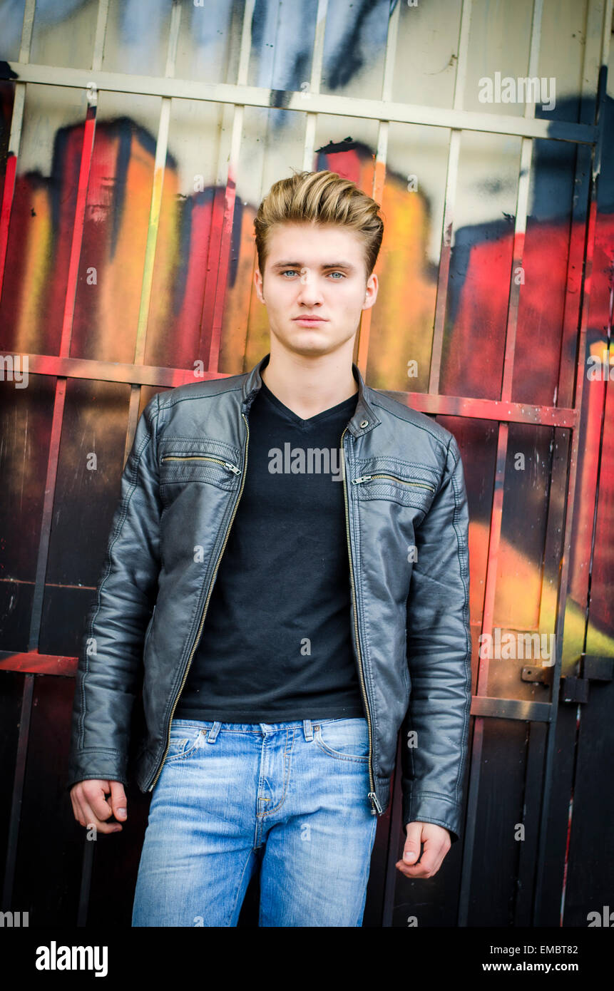 Attractive blond haired young man standing against graffiti wall, looking at camera - Stock Image