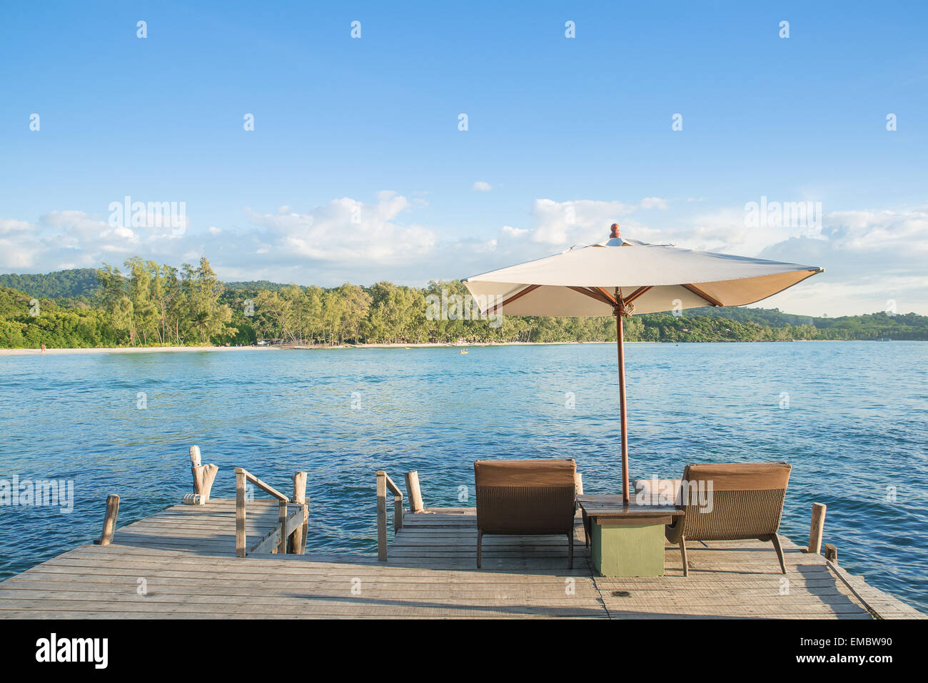 Summer, Travel, Vacation and Holiday concept - Beach chairs and umbrella on wooden desk against blue sky in Phuket,Thailand - Stock Image