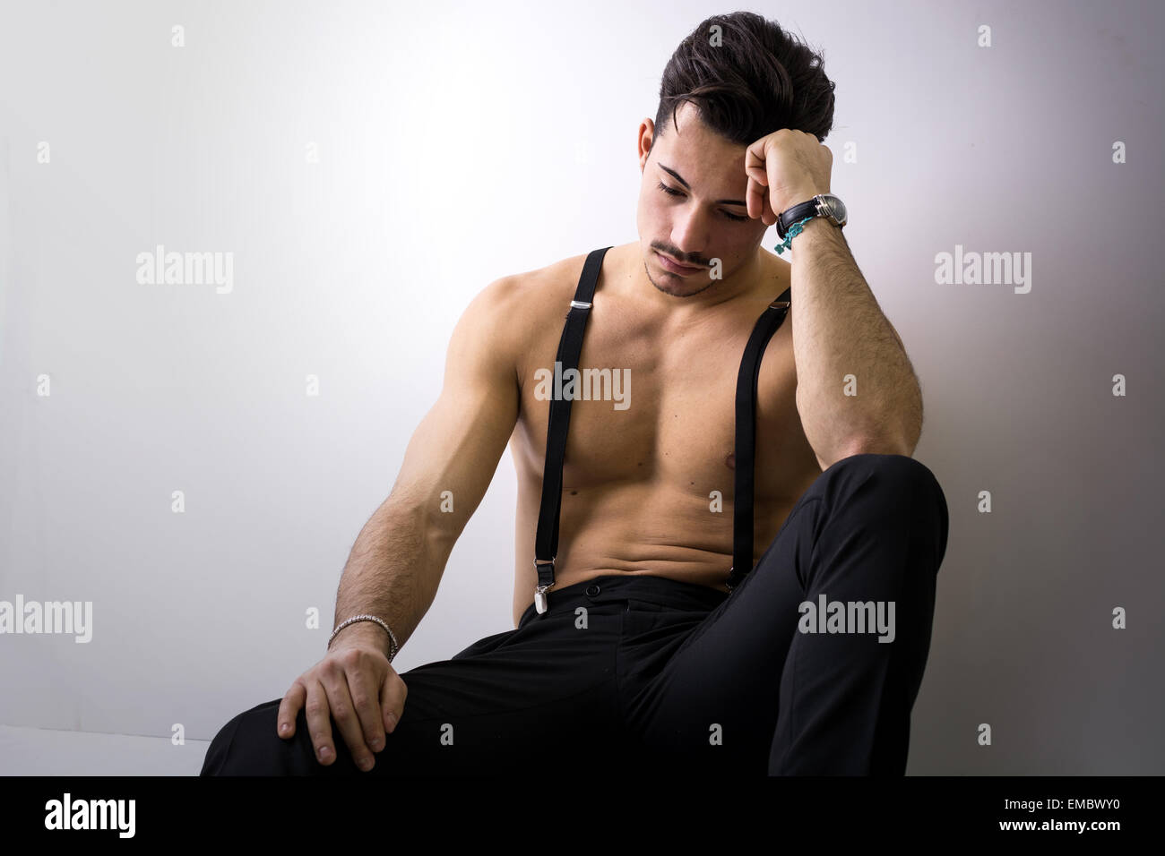 Shirtless athletic young man with suspenders and black pants sitting on floor, looking down sad - Stock Image