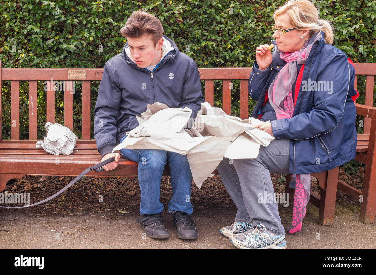 A mother and son eating fish & chips on a park bench in the Uk - Stock Image
