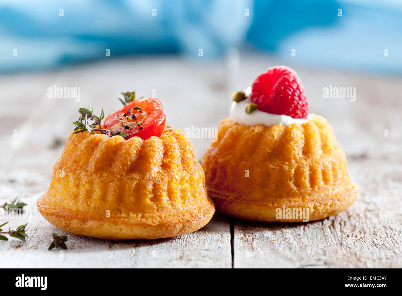 Two mini Gugelhupf filled with cream cheese and ricotta garnished with tomato and raspberry - Stock Image