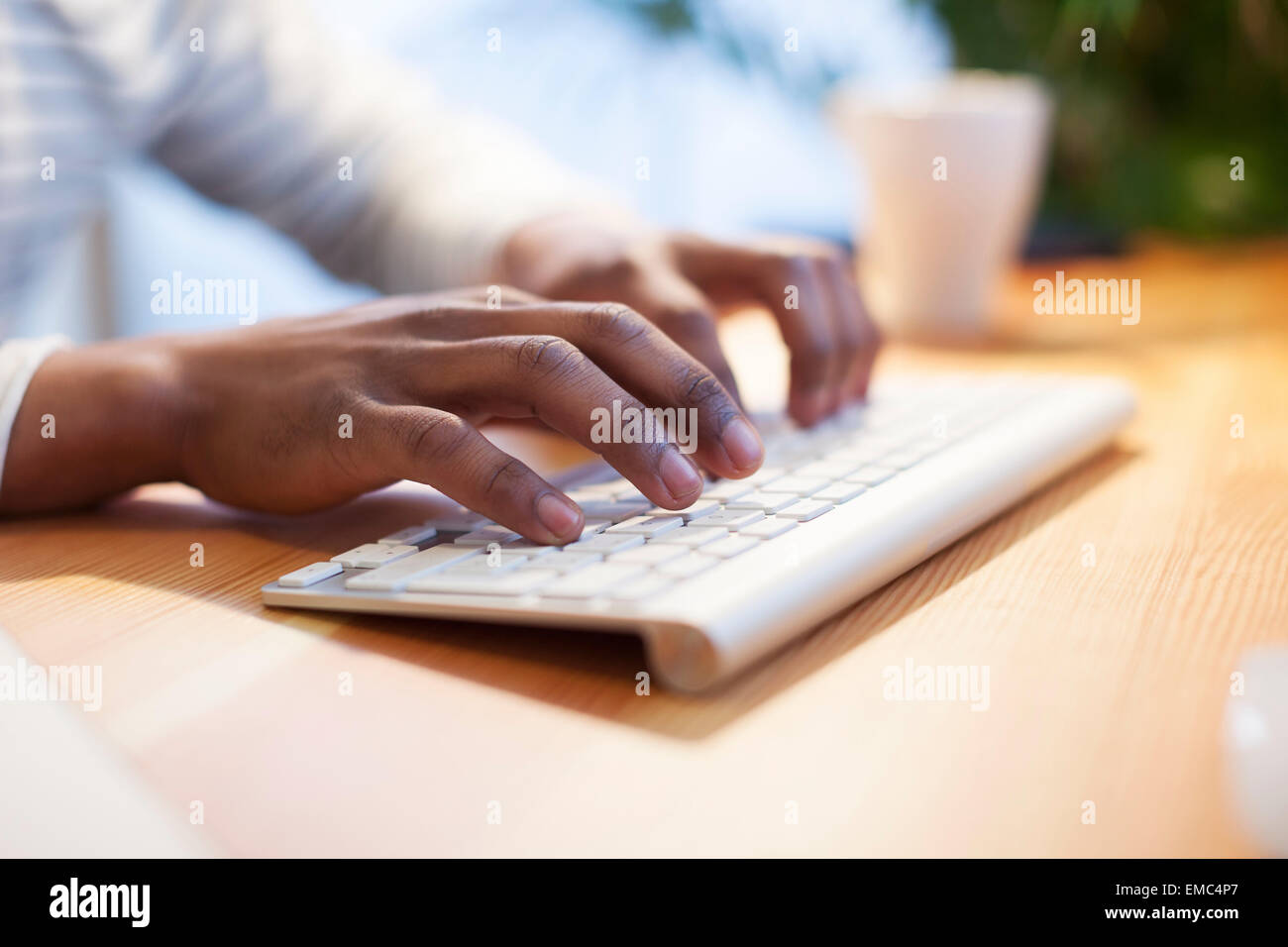 Man's hands typing on computer keyboard - Stock Image