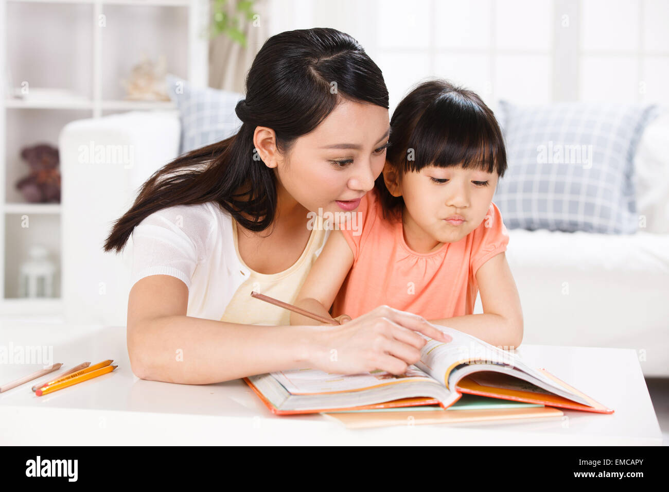 Mother guiding daughter study in the living room - Stock Image