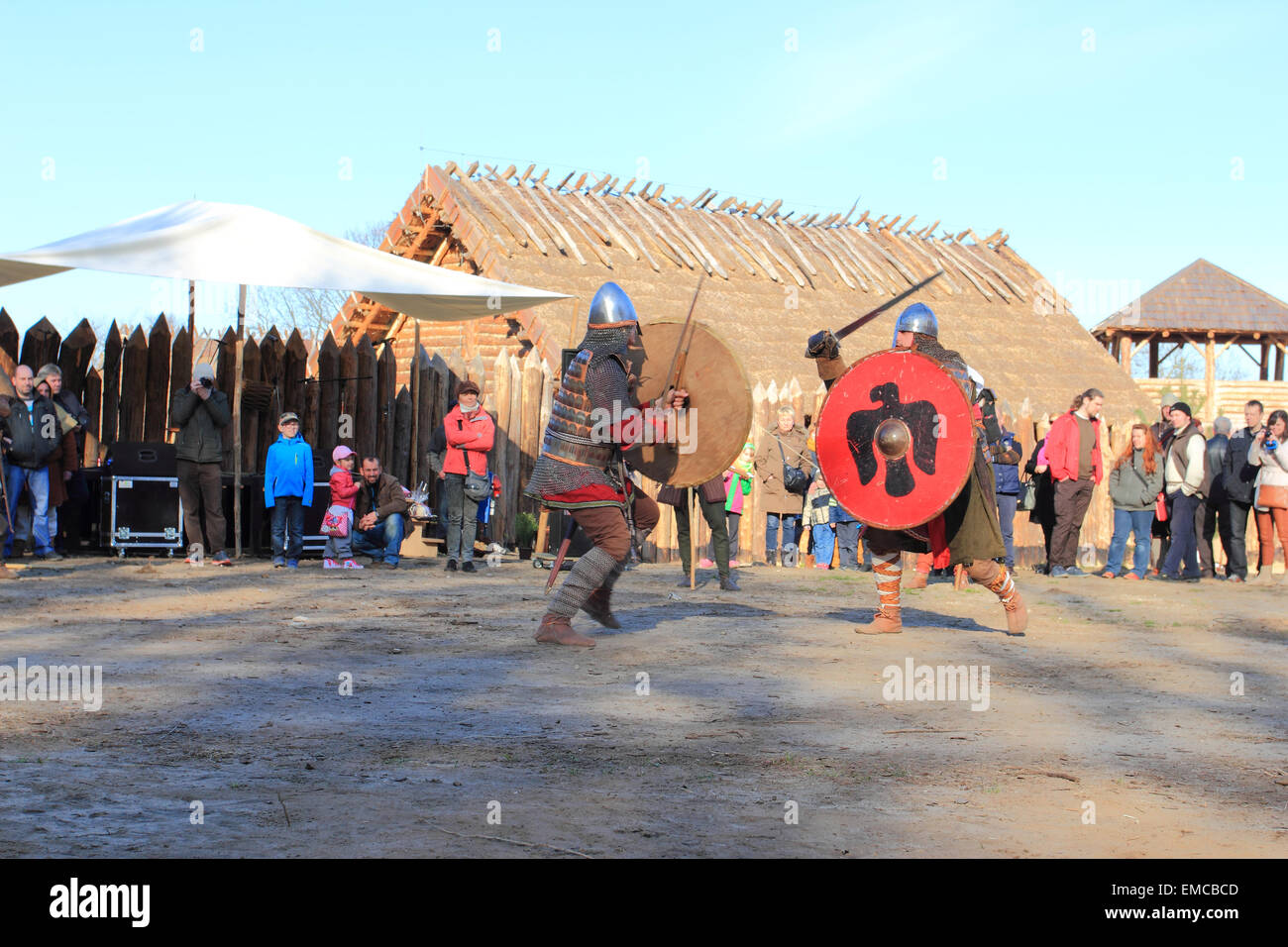Two warriors in medieval costumes fight in acting battle for tourists in Slawutowo village, Pomerania region, Poland. - Stock Image