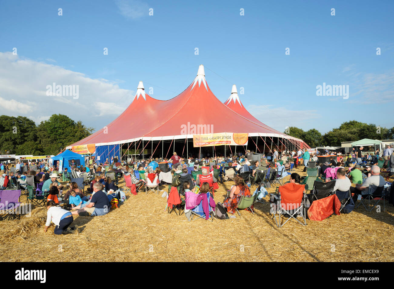 People sitting enjoying the evening sun in front of the main stage at the Wickham Music Festival, Hampshire, England - Stock Image