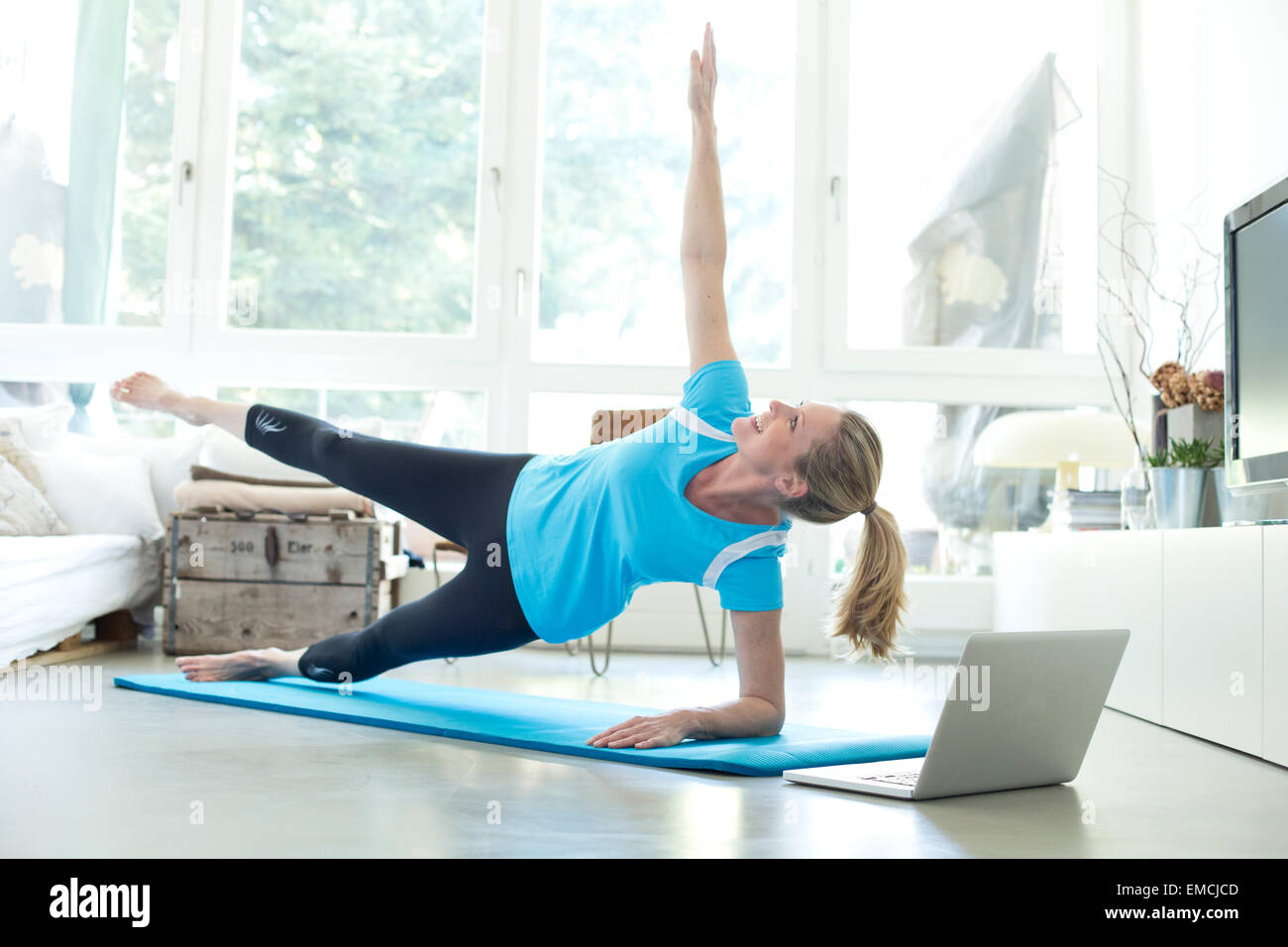 Woman with laptop exercising on gym mat in living room stock photo