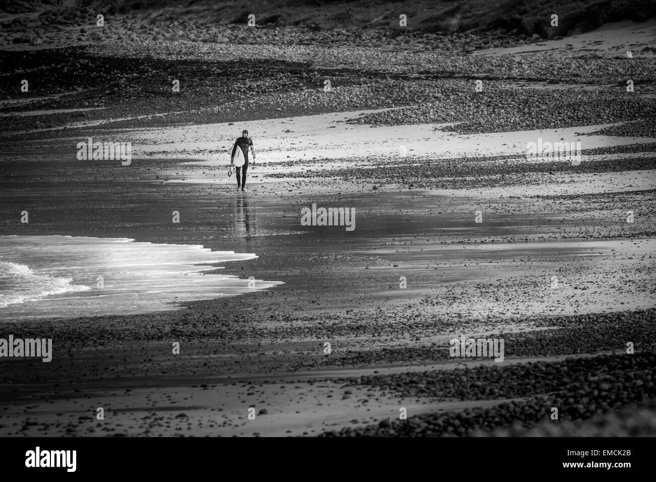 Lone surfer on the sands of Traigh Siar, Vatersay, Isle of Barra, Outer Hebrides, UK - Stock Image
