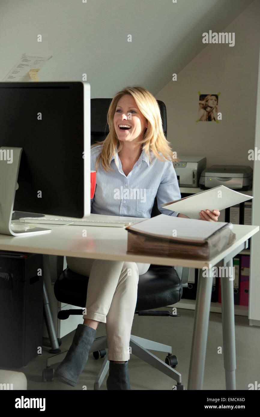 Happy woman looking at computer monitor at home - Stock Image
