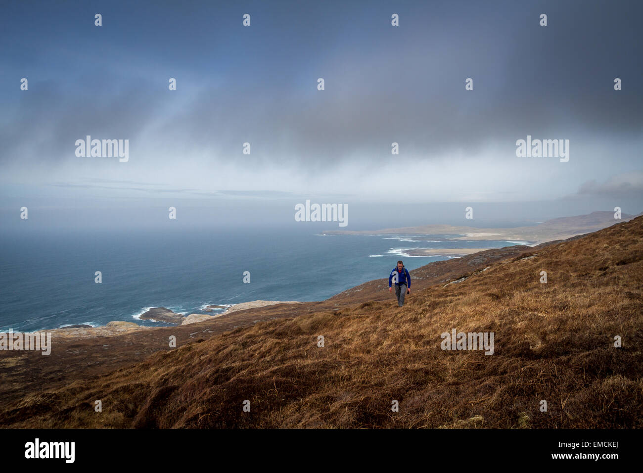 Walker ascending hill from Tangasdale and Dun Ban, Isle of Barra, Outer Hebrides - Stock Image