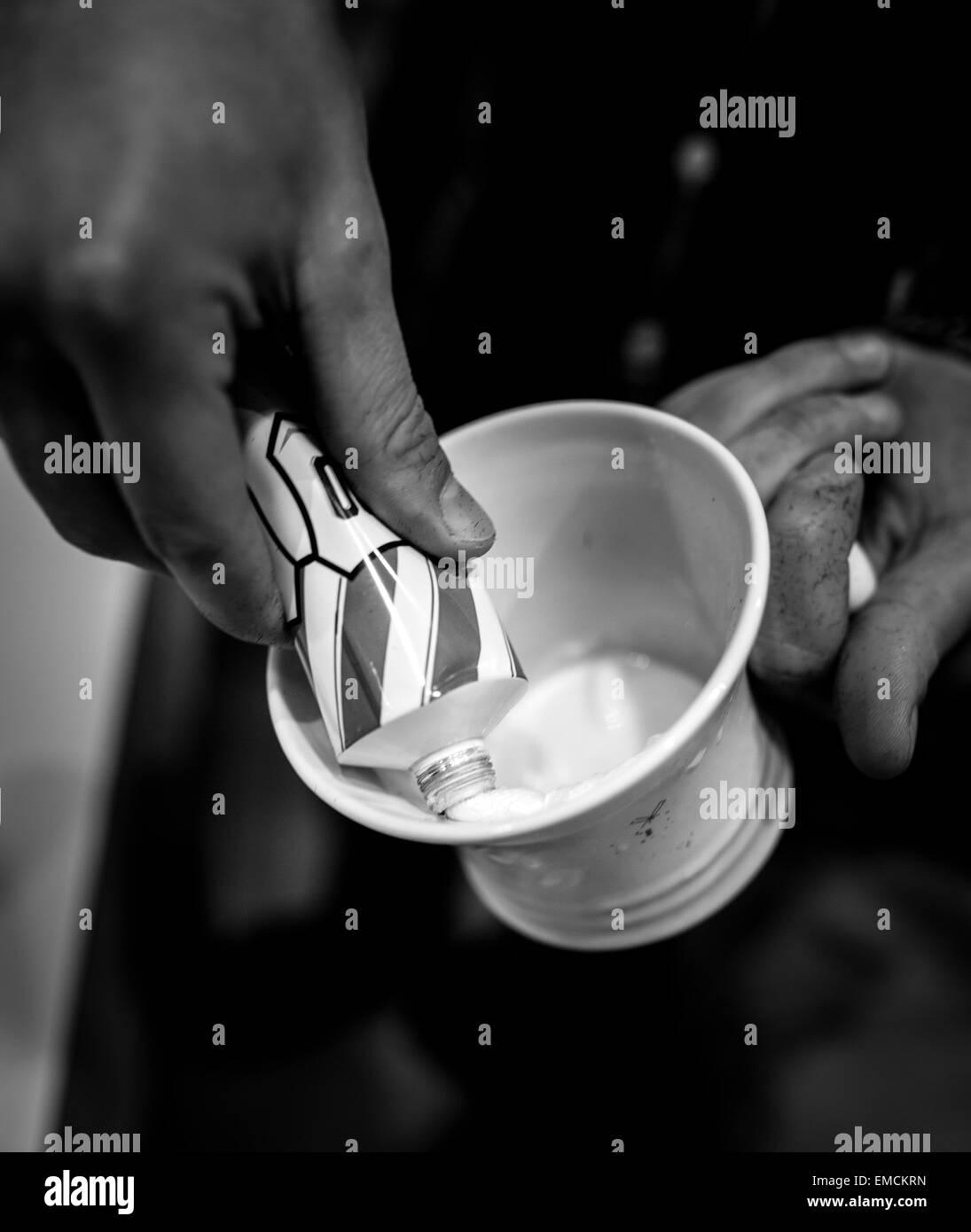 Man's hand pressing tube of shaving cream - Stock Image