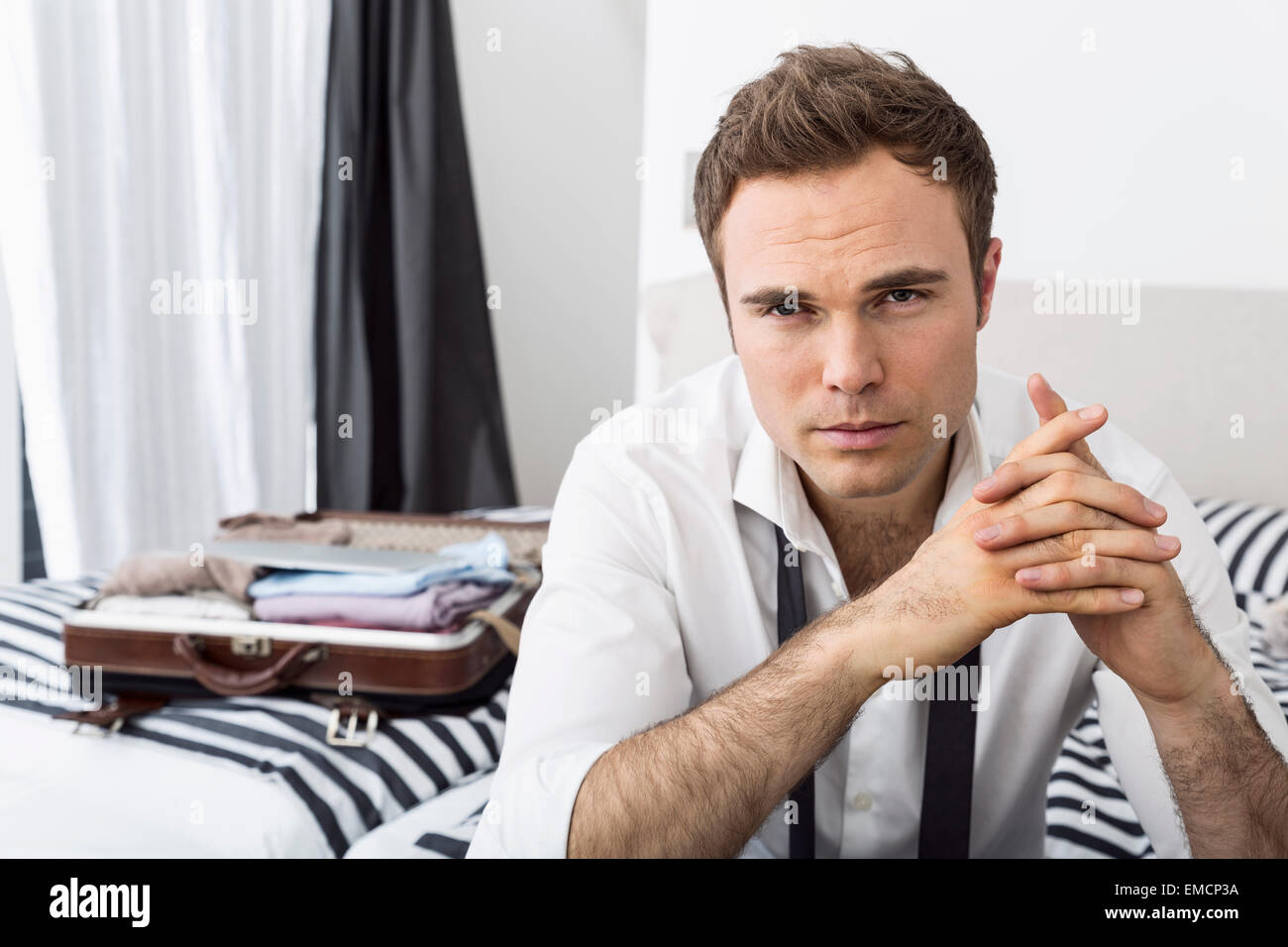 Businessman sitting on bed with clasped  hands - Stock Image