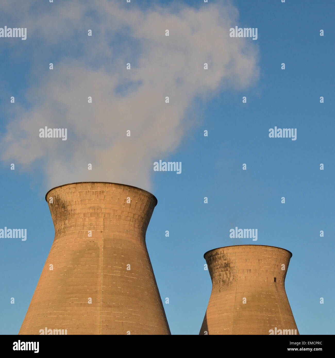Two hyperboloid cooling towers in late evening sunlight - Stock Image