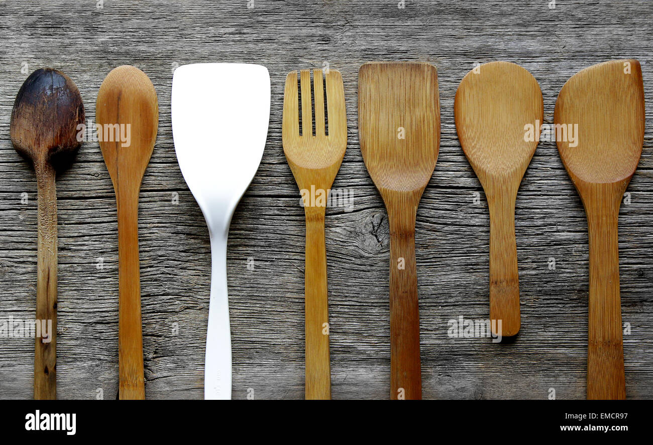 vintage kitchen spatulas and spoons on  board with one standing out from the crowd - Stock Image