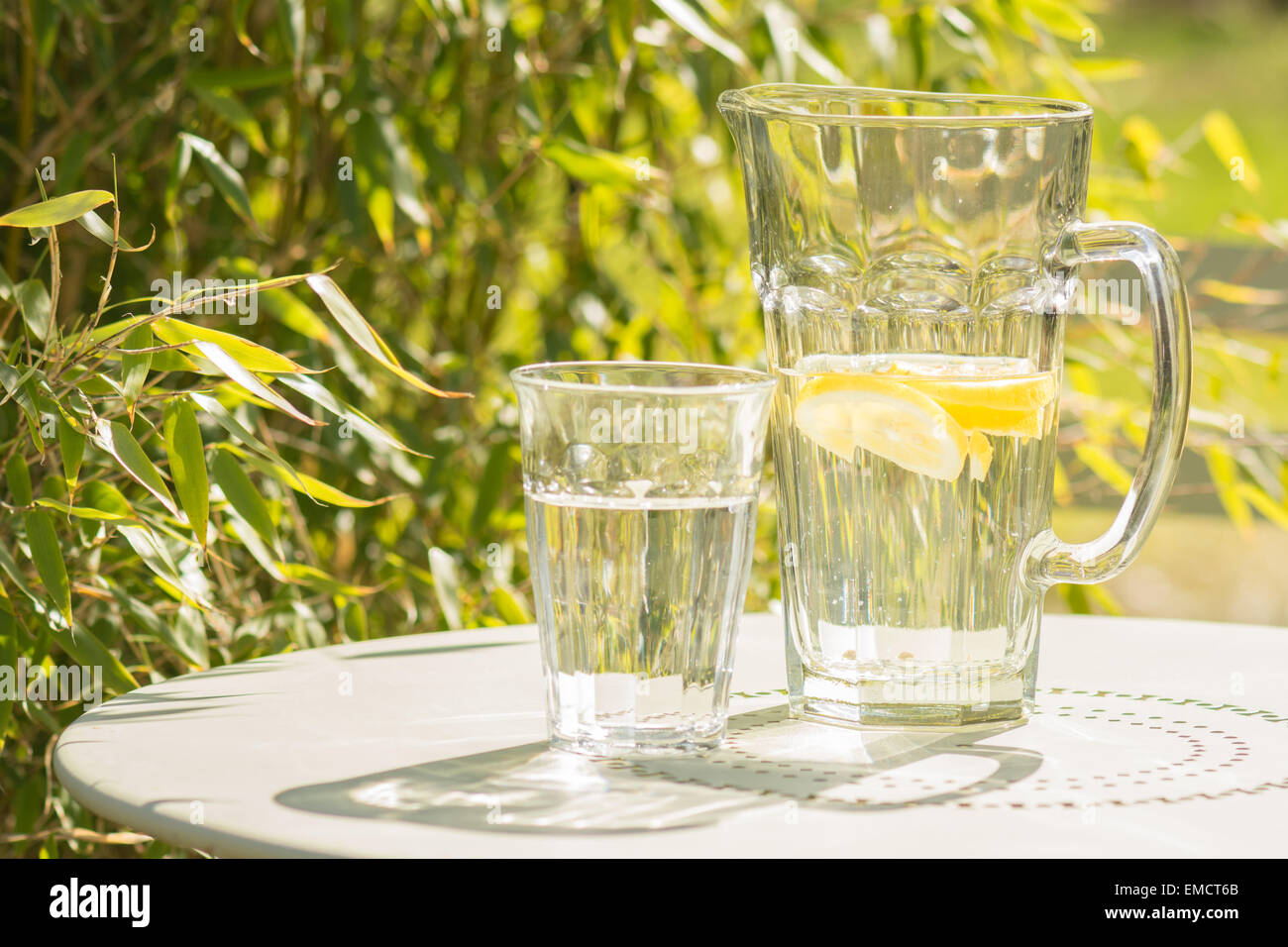 Summer - reflections of sun shining through jug and glass of lemon water on green bistro table on garden terrace - Stock Image