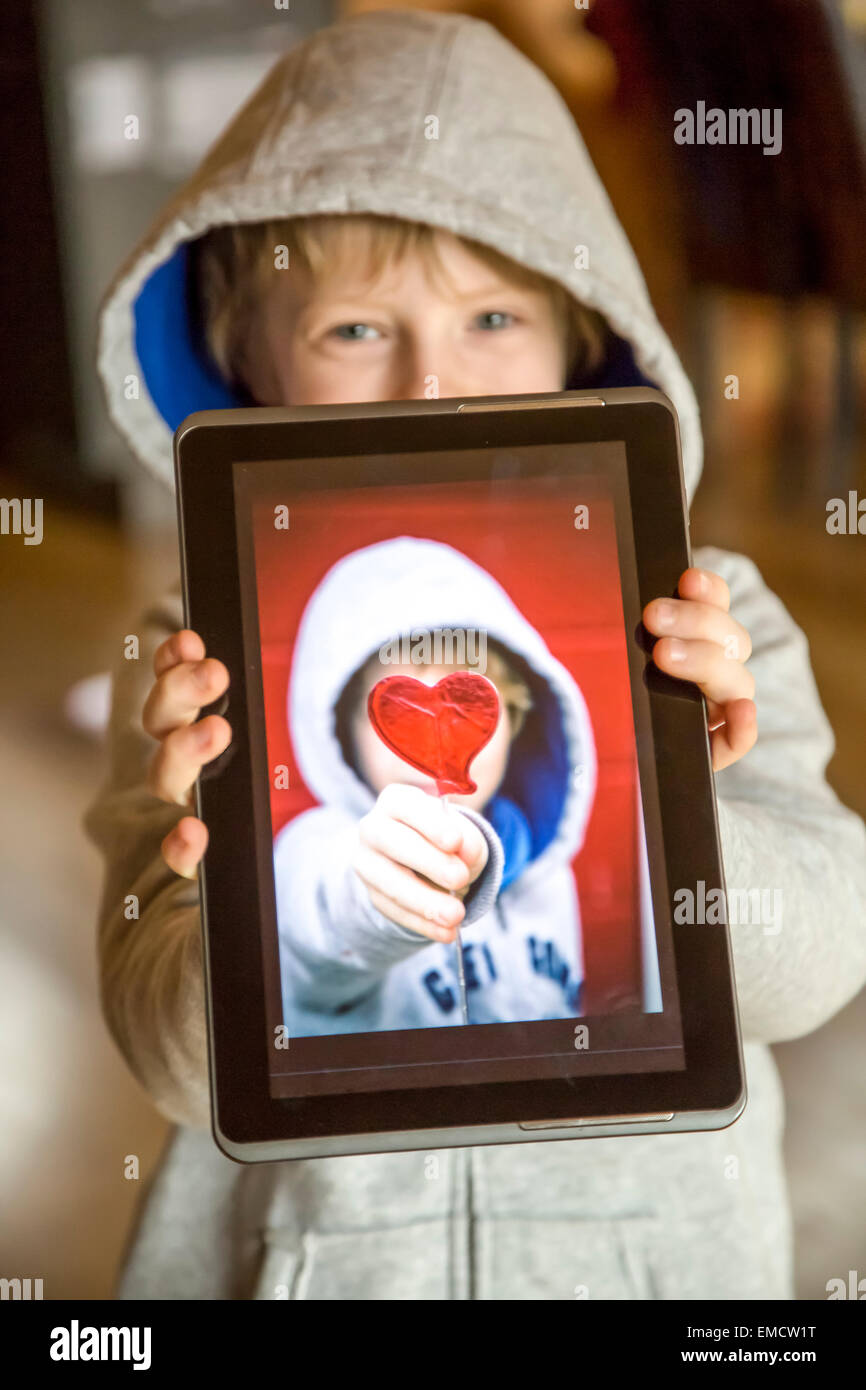 Boy showing digital tablet with photography of himself - Stock Image
