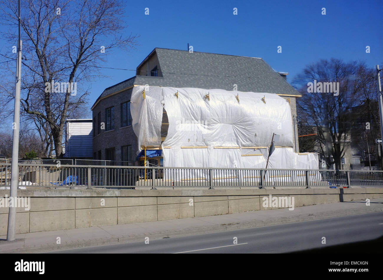 A Canadian house half covered in white plastic sheeting in Ontario. - Stock Image