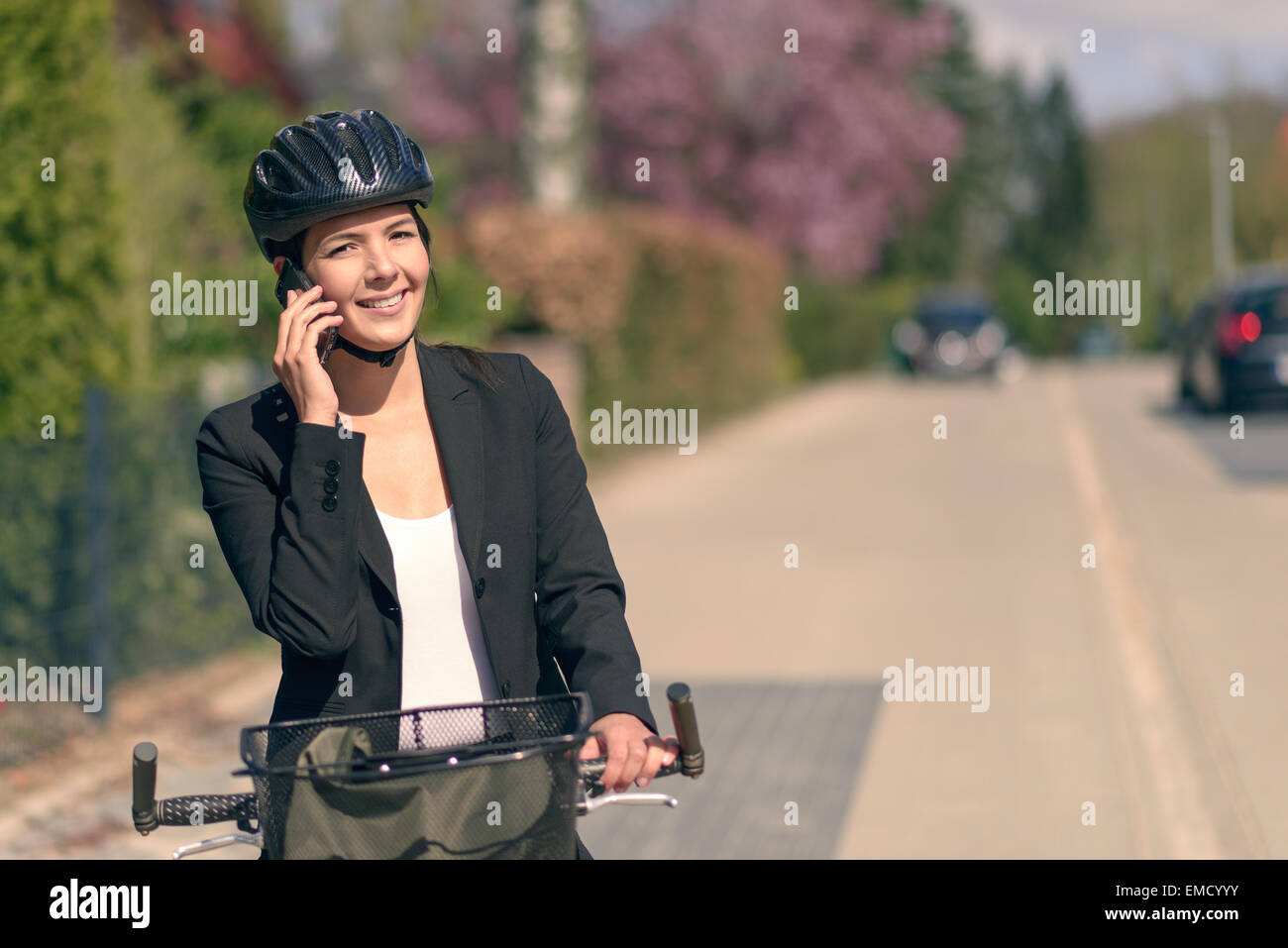 Stylish friendly young businesswoman riding to work pausing to answer a call on her mobile phone standing supporting - Stock Image