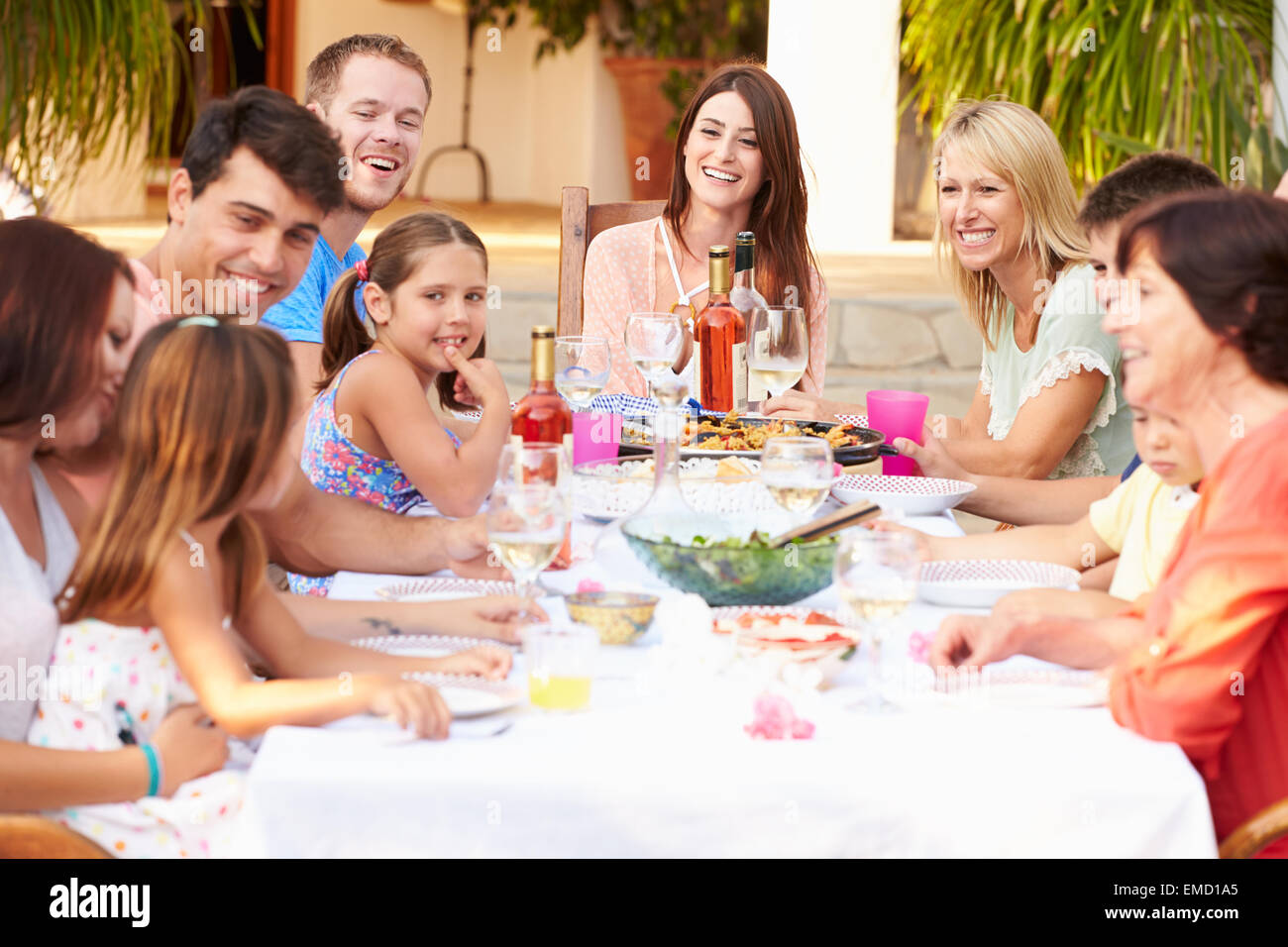 Large Family Group Enjoying Meal On Terrace Together - Stock Image