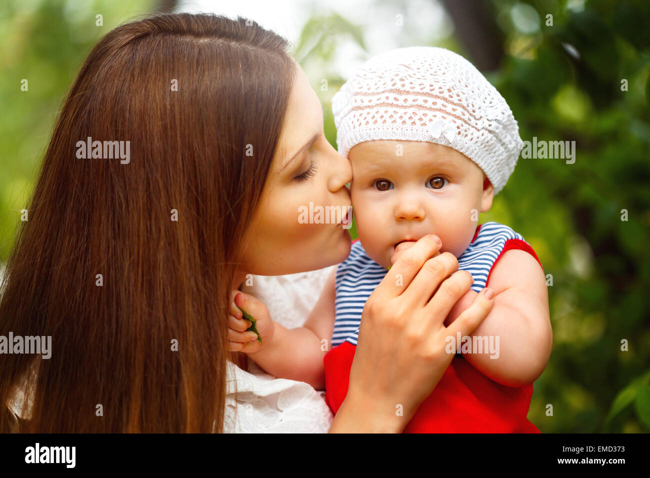 Surprised Toddler Baby Girl sitting on Mom`s Hands, looking into camera. Mother kissing the kid. Relaxing in green - Stock Image