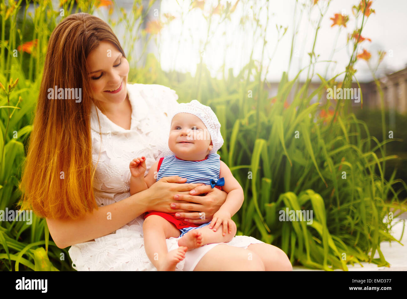 Cute smiling Toddler Baby sitting on Mom`s knees and having Fun. Relaxing in green summer Park. Selective focus. - Stock Image