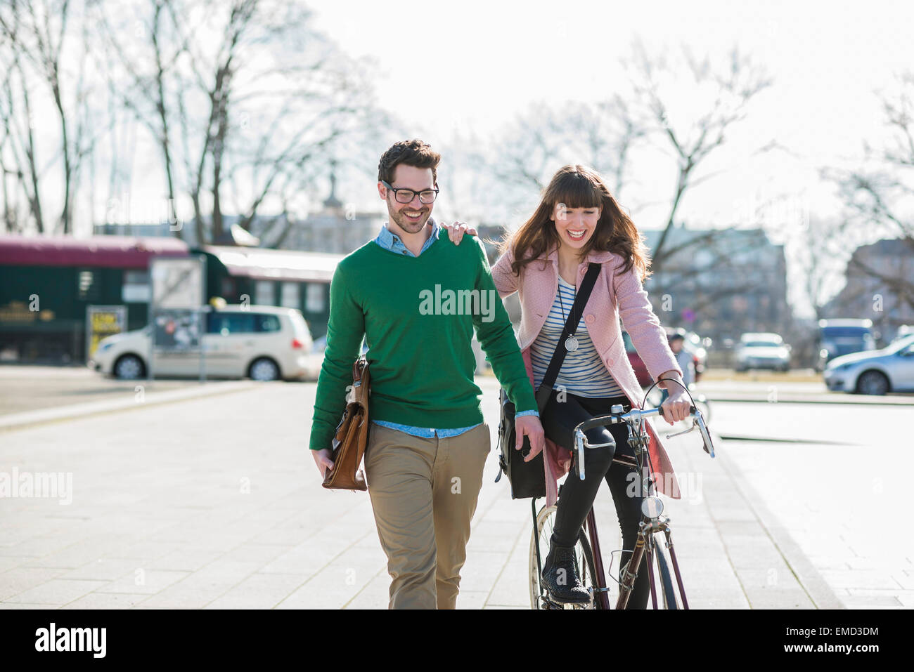 Happy couple going home together, woman riding bicycle - Stock Image