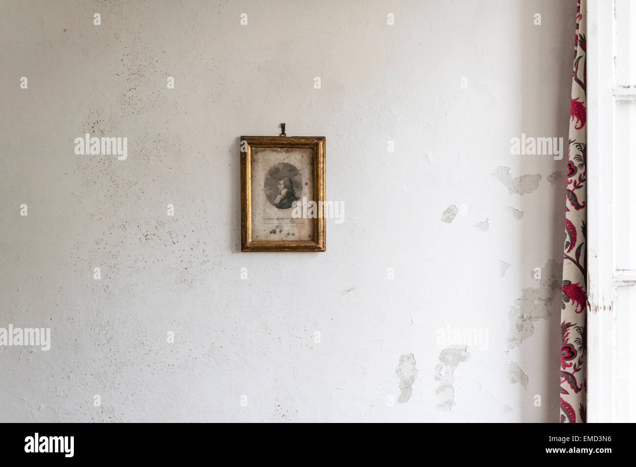 Italy. An old and badly foxed print in a gilt frame hanging on a damp and crumbling wall - Stock Image