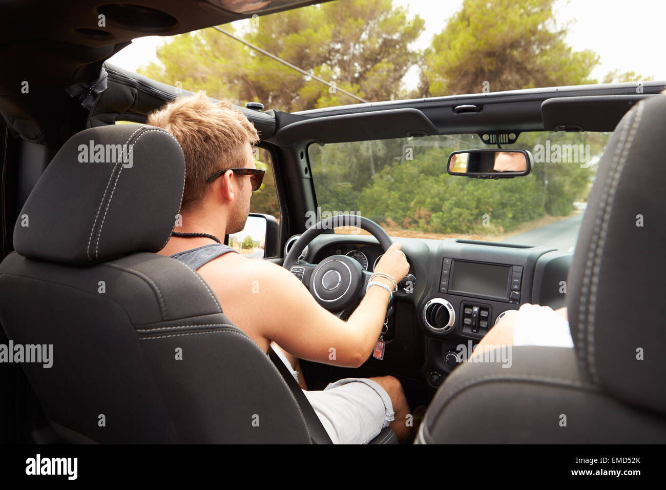 Man Driving Open Top Car Along Country Road - Stock Image