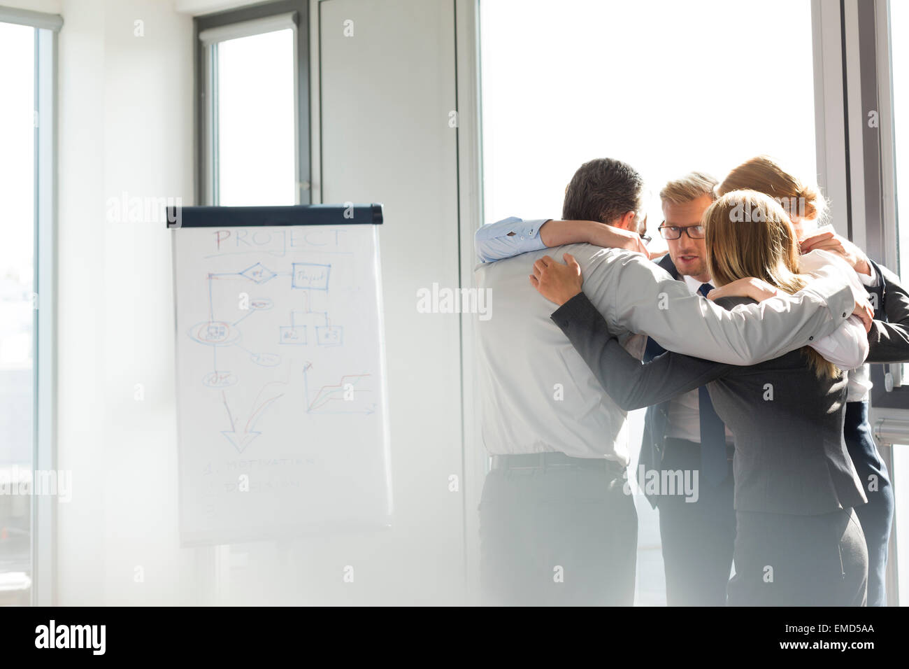Business people standing in circle, arms around - Stock Image