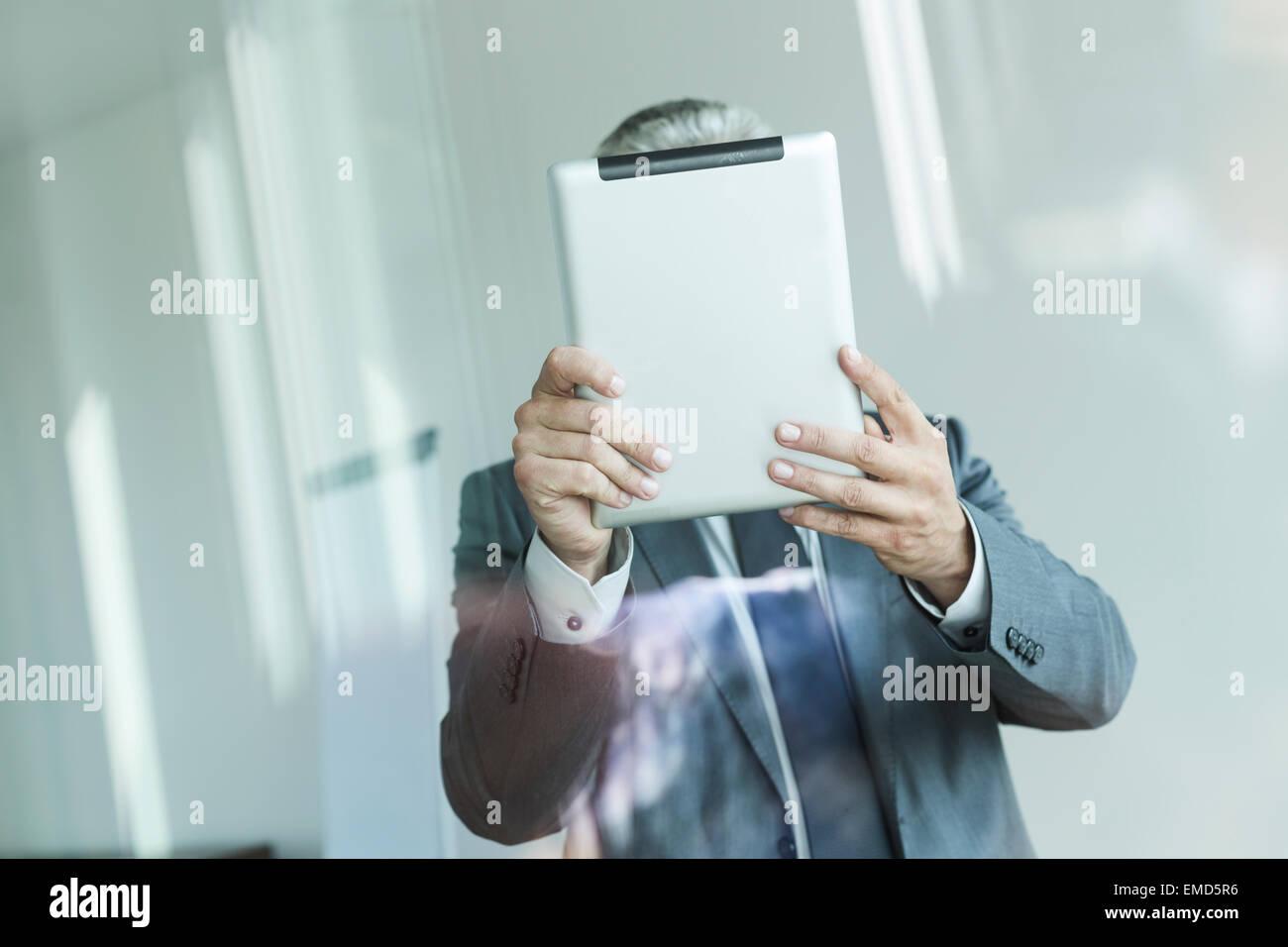 Businessman holding digital tablet, face obscured - Stock Image