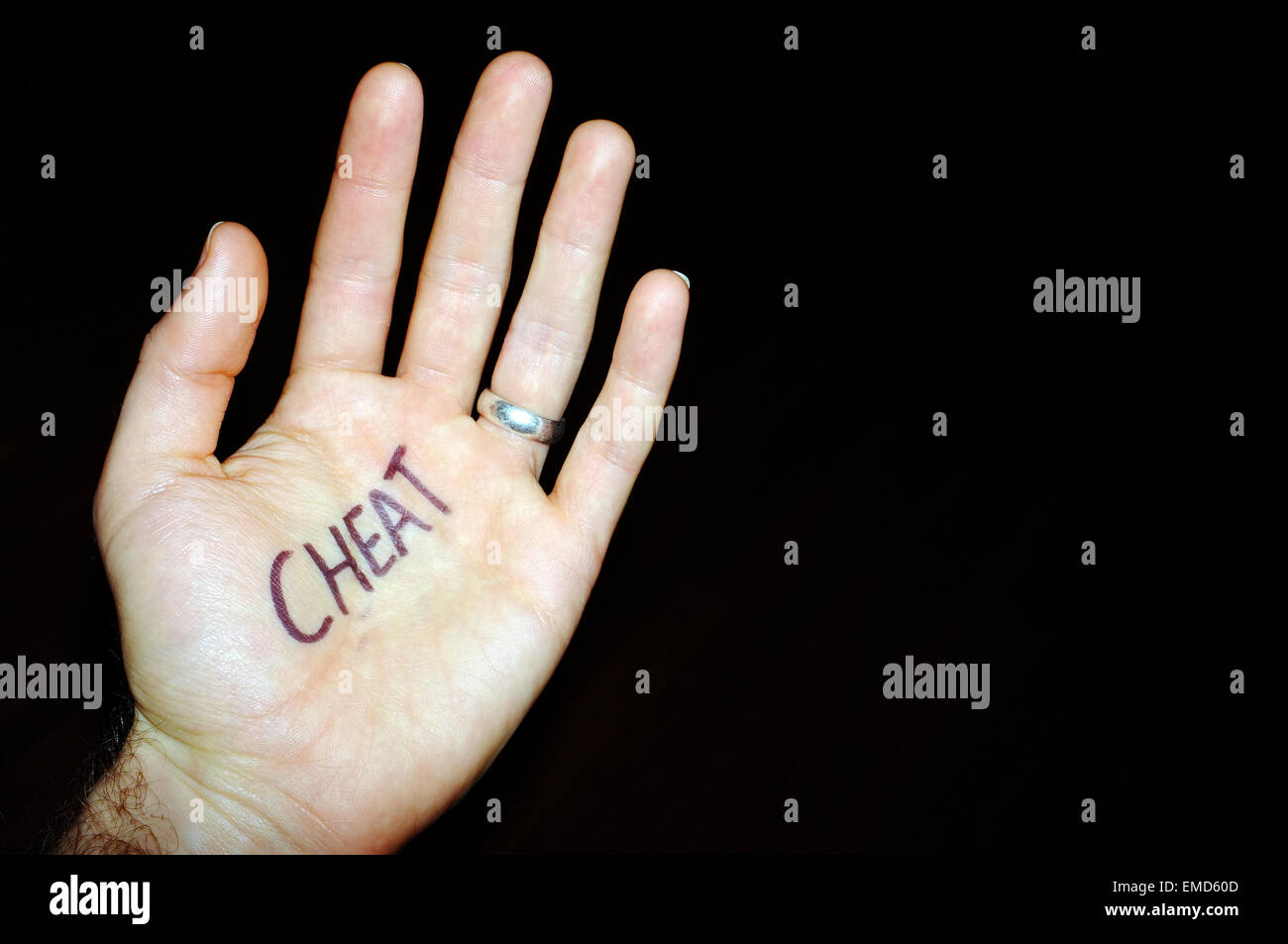 Cheat written on a white man's hand photographed against a black background. - Stock Image
