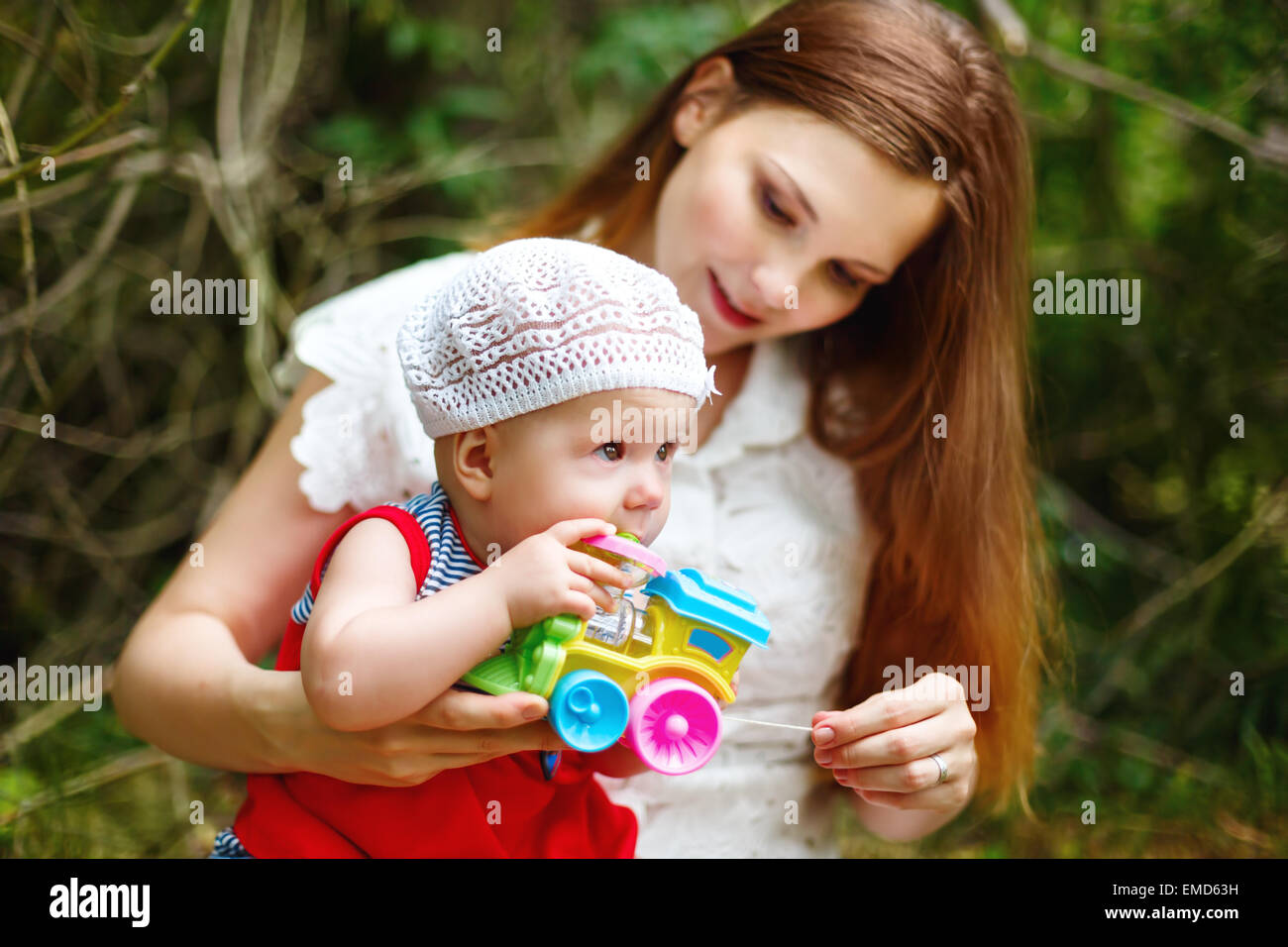 Cute Toddler Baby Girl sitting on Mom`s Hands, playing with Toy. Relaxing in green summer Park. Selective focus - Stock Image