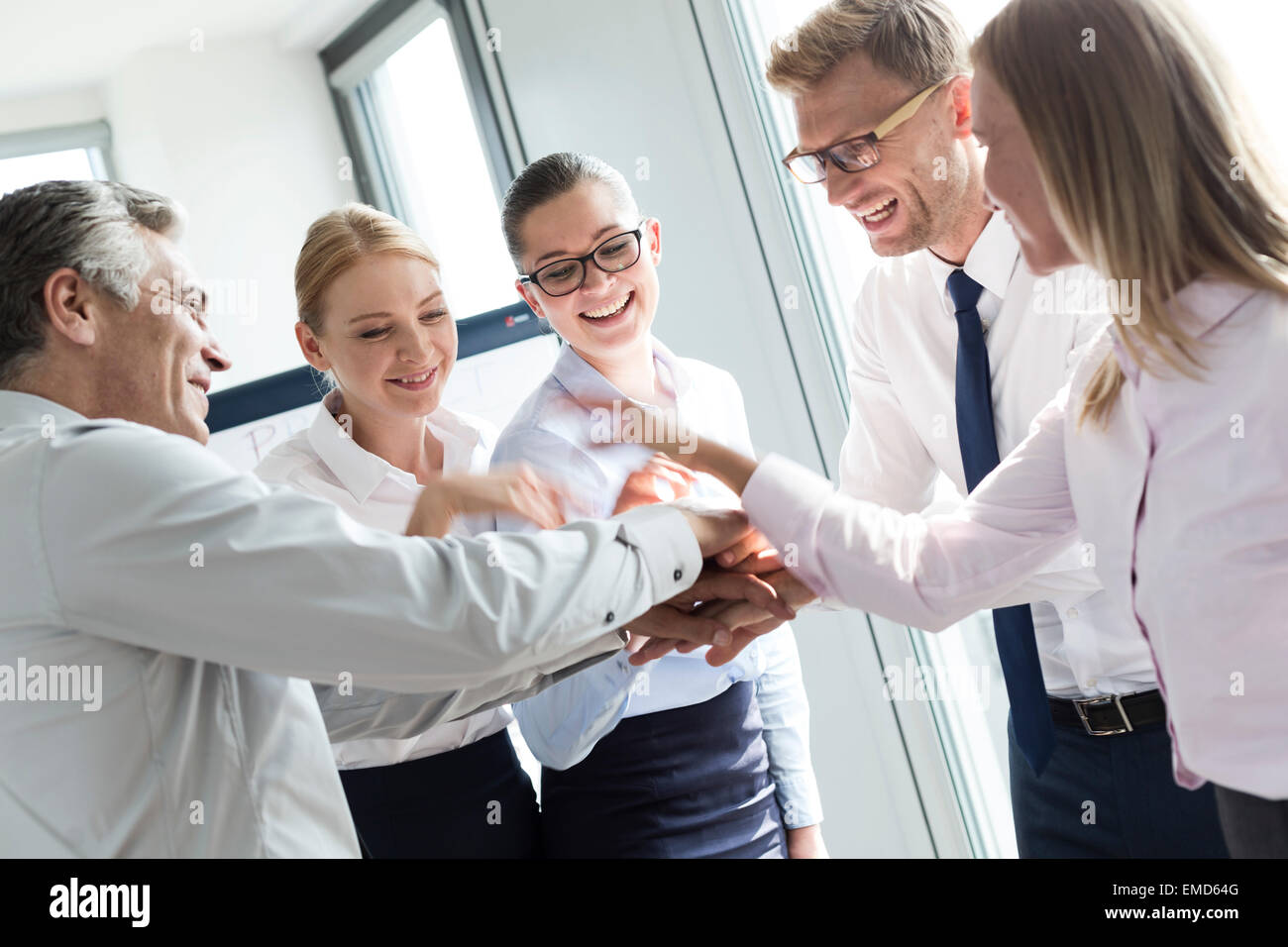 Business people with piled hands, bonding for success - Stock Image