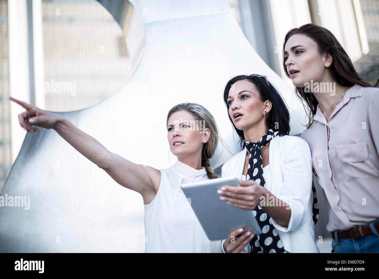 Three women with digital tablet in the city Stock Photo