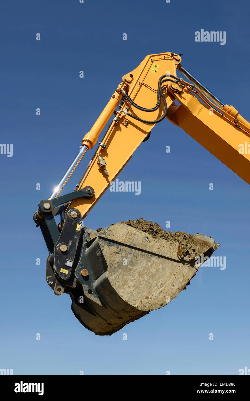 A yellow digger jib with a bucket full of soil - Stock Image
