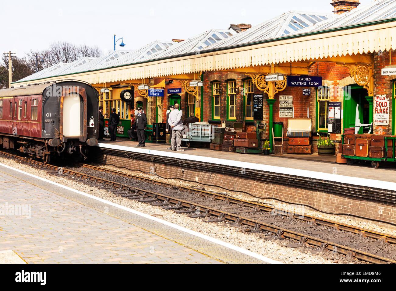 Sheringham station platform train luggage passengers waiting track rail railway line North Norfolk UK England - Stock Image