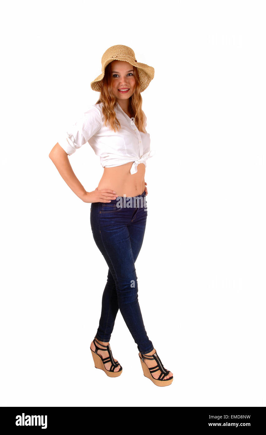 A Beautiful Slim Woman In Jeans And A White Blouse Wearing A Straw