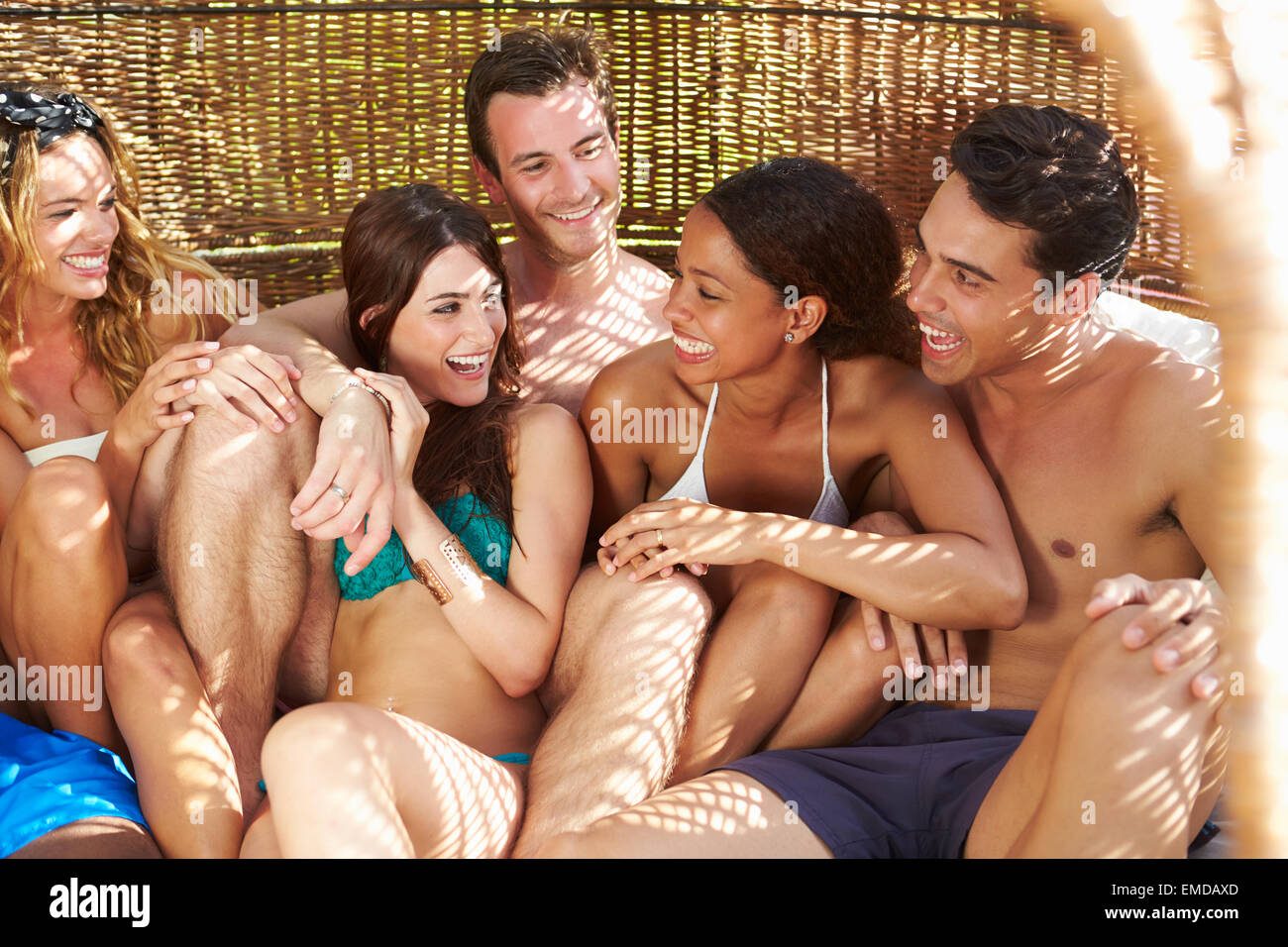 Group Of Friends In Swimwear Relaxing Outdoors Together - Stock Image