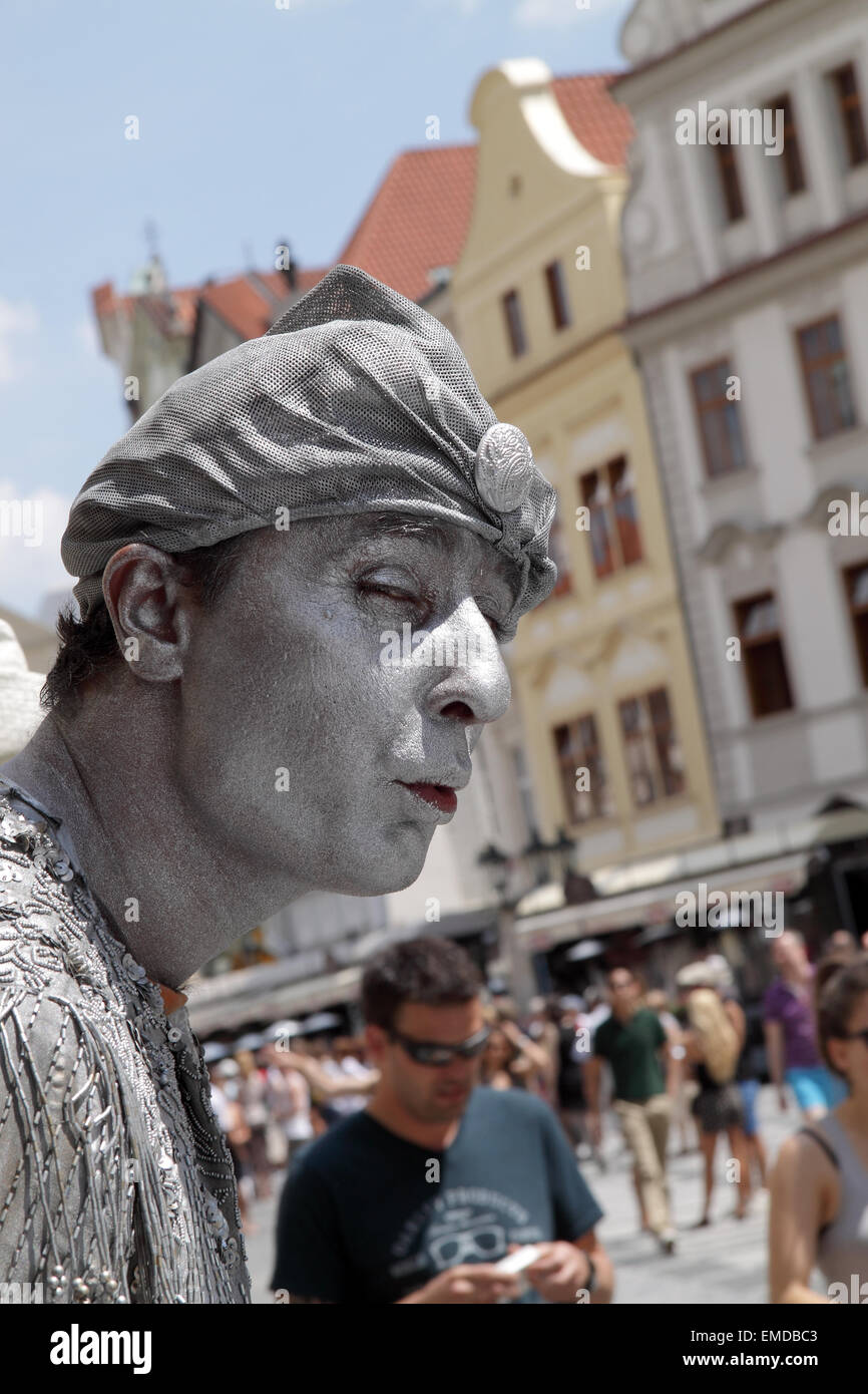 Male Street performer dressed and painted in silver, performs on Stare Mesto Square in Prague, with tourists in Stock Photo