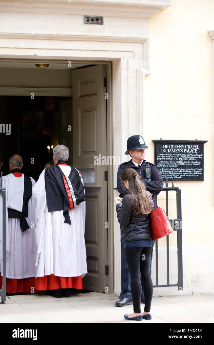 Clergy entering the Queens Chapel with a policeman on guard duty in London England - Stock Image