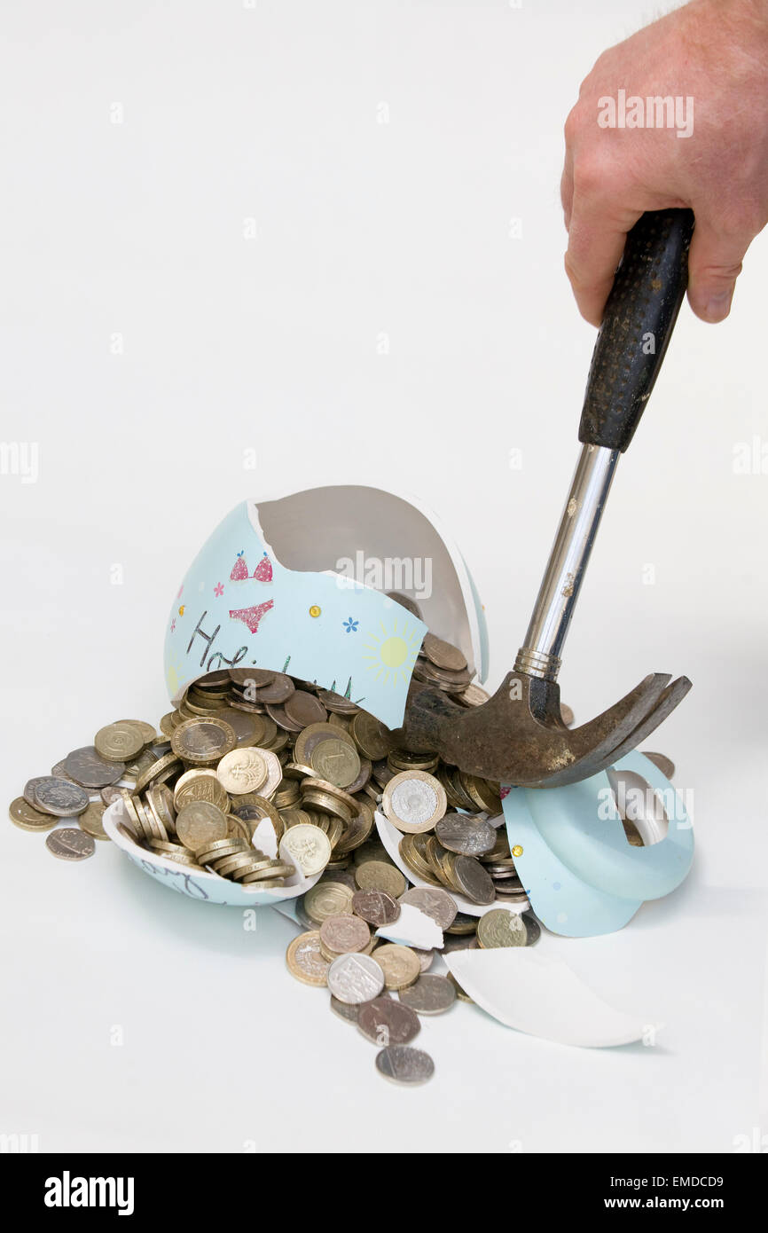 Man with a hammer smashing a Money box full of Coins pouring out of it on a white background - Stock Image