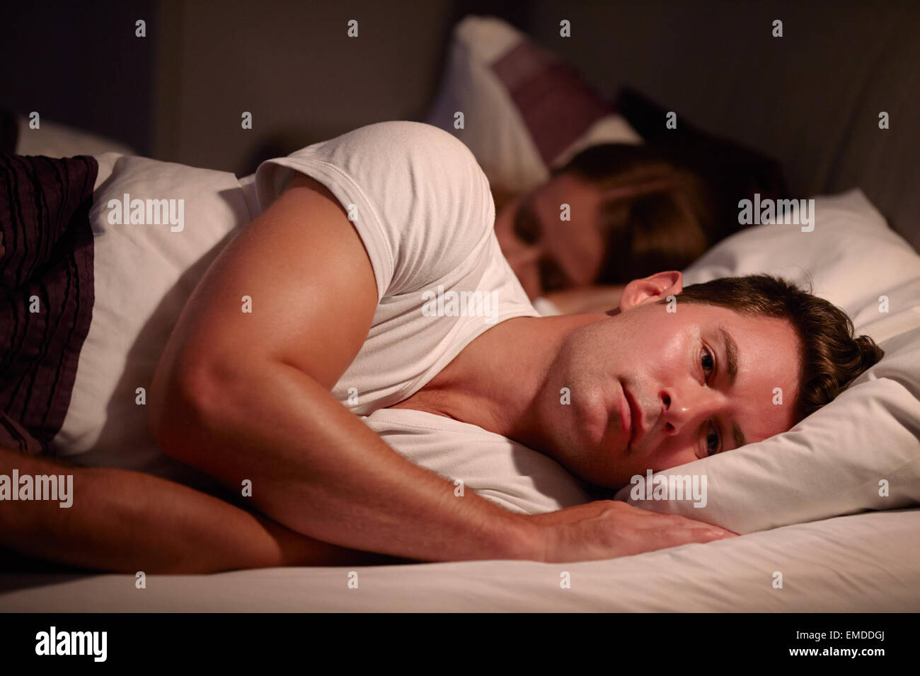 Man Lying Awake In Bed Suffering With Insomnia - Stock Image