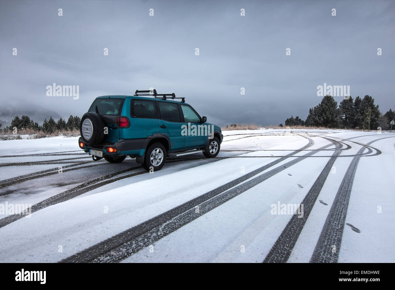 All terrain car on a snowed road. - Stock Image