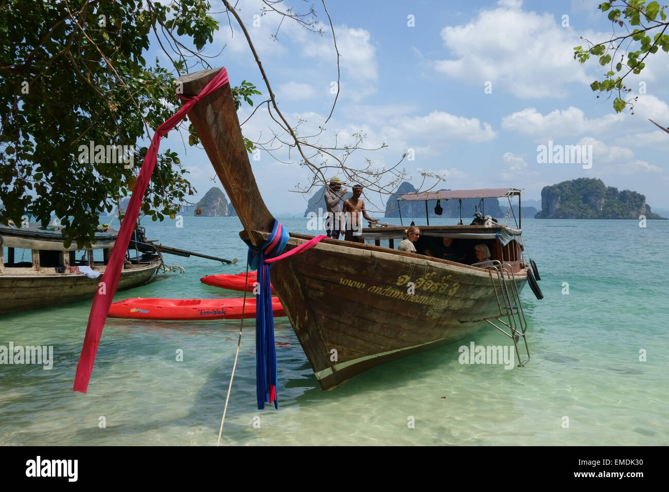 A tourist longtail boat moored with kayaks on a beach on Koh Hong in the Andaman Sea off Krabi Province in Thailand - Stock Image